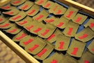 Throwback patches, hand made by members of the 1st Combat Aviation Brigade on deployment in Afghanistan, are set out before being pinned on Soldiers of the unit during a combat patch ceremony Oct. 28. The patches match the specifications outlined in a memorandum published in 1918, which first outlined the requirements of the patch.
