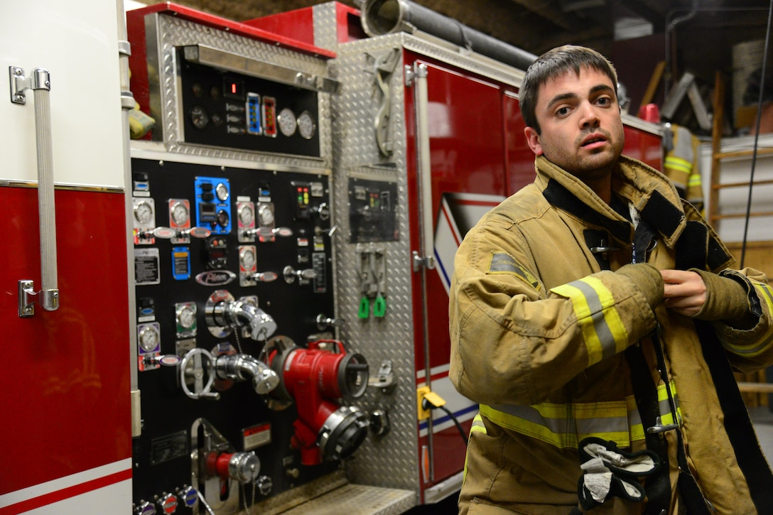 1st Lt. Anthony Perkins, 490th Missile Squadron intercontinental ballistic missile combat crew commander, puts on the gear he wears as a volunteer firefighter Nov. 8, 2016, at Great Falls Gore Hill Volunteer Fire Department, Great Falls, Mont. Perkins spends the majority of his off-duty time as a volunteer firefighter and as an ambulance emergency medical technician for Great Falls Emergency Services. (U.S. Air Force photo/Airman 1st Class Magen M. Reeves)