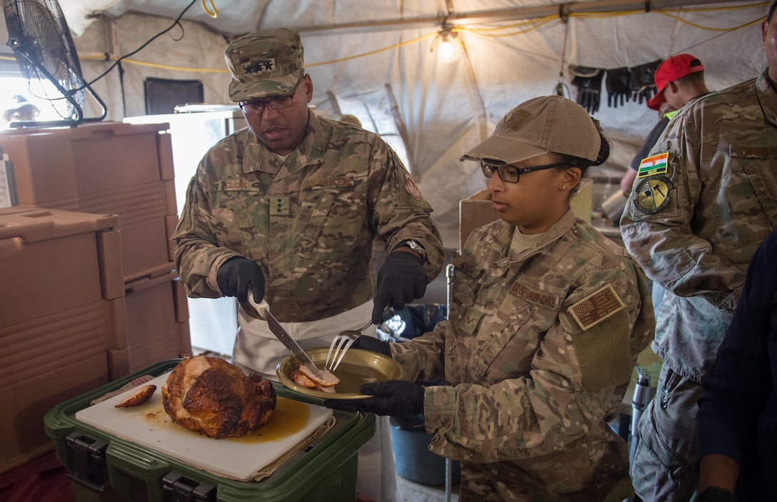 Lt. Gen. Richard Clark, 17th Expeditionary Air Force commander, serves Thanksgiving lunch to Airmen assigned the 724th Expeditionary Air Base Squadron at Air Base 201 in Agadez, Niger, during a visit Nov. 24, 2016. During a three day trip, Clark visited Airmen in Europe and Africa who support the Air Force's intelligence, surveillance and reconnaissance mission. This was Clark's first visit to NAS Sigonella, Niamey and Agadez as 3rd Air Force commander. (U.S. Air Force photo by Tech. Sgt. Ryan Crane)