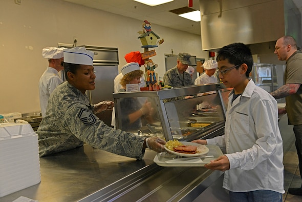 U.S. Air Force Senior Master Sgt. Tameka Taylor, 20th Contracting Squadron superintendent, serves food to a Team Shaw member at the Chief Master Sgt. Emerson E. Williams Dining Facility at Shaw Air Force Base, S.C., Nov. 24, 2016. As part of a holiday season tradition, commanders, chiefs and first sergeants volunteered their time to help the dining facility staff serve food to the Team Shaw community. (U.S. Air Force photo by Airman 1st Class Destinee Sweeney)