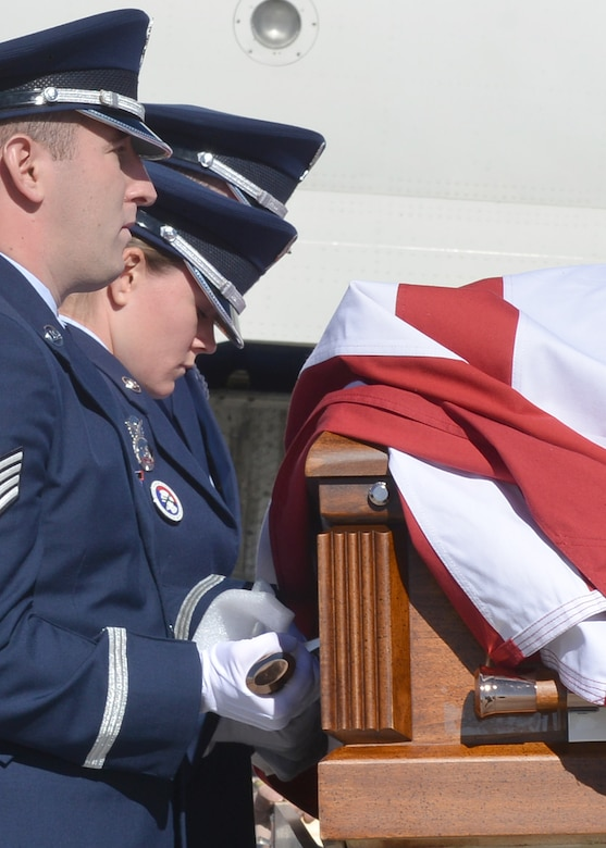Kirtland Air Force Base Honor Guard members act as pallbearers for Tech. Sgt. Nicholas Heck on Nov. 18 as his remains arrive at the Albuquerque International Sunport en route to Cannon Air Force Base for the funeral. This dignified arrival, the primary mission of honor guards, was the first KAFB Honor Guard has performed in many years. Six Honor Guard members act as pallbearers and a seventh renders a salute. Heck was stationed at Cannon before transferring to Yakota Air Base, Japan, where he died.