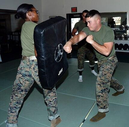Lance Cpl. Darin Brooks, (right), Marine Corps Martial Arts Program student, Marine Corps Logistics Base Albany, performs a rear hand punch on Pfc. Mykerria Johnson, MCMAP student, training pad, Nov. 21.