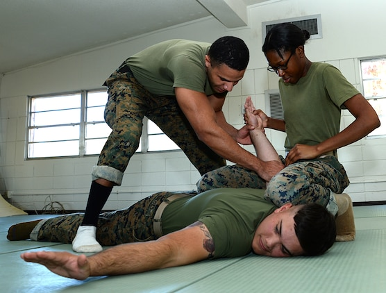 Sgt. Josue Balbuena, (left), Marine Corps Martial Arts Program instructor, Marine Corps Logistics Base Albany, demonstrates to Pfc. Mykerria Johnson, MCMAP student, how to properly conduct an escort noncompliant take-down on Lance Cpl. Darin Brooks, MCMAP student, Nov. 21.