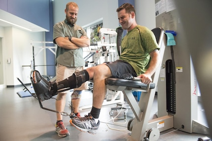 Wayne Strube (left), a former Air Force security forces patrolman, coaches Army Staff Sgt. Lennis Lebarge as he rehabs his right knee with the Delfi machines BFR tourniquet at the Center for the Intrepid, or CFI, at Joint Base San Antonio-Fort Sam Houston Sept. 13. The BFR tourniquet reduces blood flowing from the specific body part and expedites the healing process. Strube currently serves military service members as the CFI physical therapist in charge of the Return to Run program.