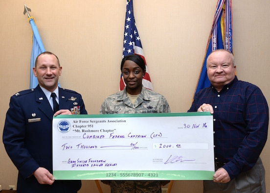 Tech Sgt. Jessica Young, non-commissioned officer in-charge of unaccompanied housing assigned to the 28th Civil Engineer Squadron, and Kevin Ott, special events coordinator, present Col. Gentry Boswell, commander of the 28th Bomb Wing, inside his office at Ellsworth Air Force Base, S.D., with a check of $2,000 in donations Nov. 30, 2016. On behalf of the Air Force Sergeants Association Chapter 951, donations were collected from members of the base to go toward the Combined Federal Campaign, the world's largest and most successful annual workplace charity campaign, with more than 130 CFCs located everywhere federal employees work. (U.S. Air Force photo by Senior Airman Anania Tekurio/Released)