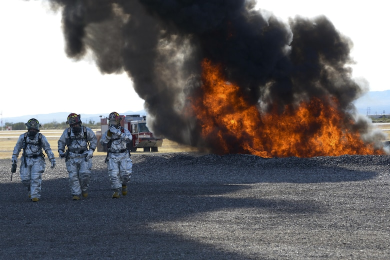 Members of the 355th Civil Engineer Squadron's fire department walk away from a fire on the fire training grounds at Davis-Monthan Air Force Base, Ariz., Nov. 28, 2016.  The fire department used recycled JP-8 jet fuel to conduct fire training as well as support the Air National Guard Air Force Reserve Command Test Center, A-10 Combined Test Force with operational testing. (U.S. Air Force photo by Senior Airman Betty R. Chevalier)