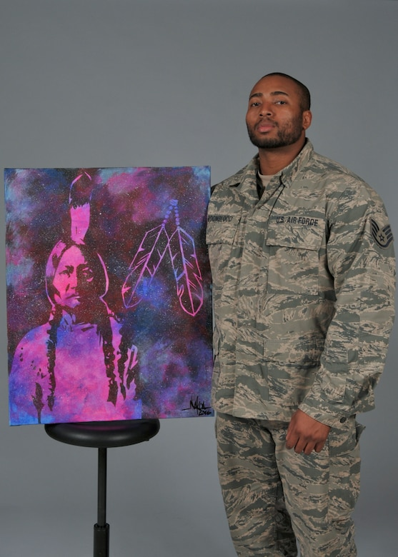 Staff Sgt. Nakoa Moonblood stands for a portrait with one of his more recent paintings Nov. 29, 2016. Moonblood recently exhibited his paintings at the Indian Summer festival in Milwaukee, Wisconsin (U.S. Air National Guard photo by Master Sgt. Kellen Kroening, 128th Air Refueling Wing Public Affairs)
