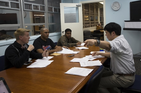 Takaatsu Sueyoshi, right, instructs students on Japanese pronunciation during a Survival Japanese Language Class Nov. 29 on Marine Corps Air Station Futenma, Okinawa, Japan. The class taught students basic speech, reading and writing skills to enrich their experience while stationed on Okinawa. During the class, the instructor demonstrated the three basic writing styles called hiragana, katakana and kanji. After the demonstration, participants practiced reading, writing and speaking basic Japanese words and phrases. Sueyoshi is a library technician and the instructor of the Survival Japanese Language class. (U.S. Marine Corps photo by Cpl. Janessa K. Pon)