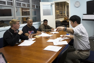 Takaatsu Sueyoshi, right, instructs students on Japanese pronunciation during a Survival Japanese Language Class Nov. 29 on Marine Corps Air Station Futenma, Okinawa, Japan. The class taught students basic speech, reading and writing skills to enrich their experience while stationed on Okinawa. During the class, the instructor demonstrated the three basic writing styles called hiragana, katakana and kanji. After the demonstration, participants practiced reading, writing and speaking basic Japanese words and phrases. Sueyoshi is a library technician and the instructor of the Survival Japanese Language class.