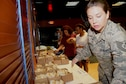 Tech. Sgt. Kirsten Cohen, 379th Expeditionary Force Support Squadron quality assurance technician, arranges sandwiches and desserts at a table inside the Fox Sports Lounge Sept. 23, 2016, at Al Udeid Air Base, Qatar. The free food was served at the Air Force Birthday Ball after-party. (U. S. Air Force photo/Tech. Sgt. Carlos J. Trevino/Released)