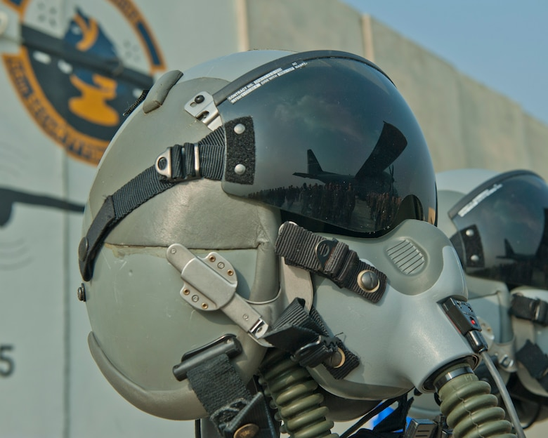 A reflection of Airmen is displayed on the visor of a pilots helmet, Bagram Airfield, Afghanistan, Oct. 2, 2016. A remembrance ceremony was held to honor those lost when TORQE 62 crash on Oct. 2, 2015. The helmets were part of a display to remember and honor the fallen. (U.S. Air Force photo by Capt. Korey Fratini)