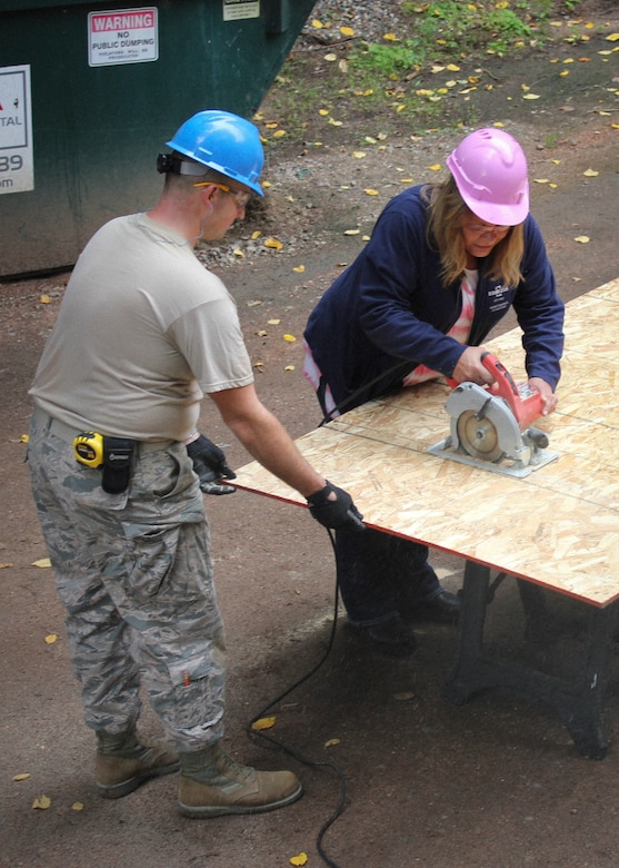 An Airman with the Civil Engineer Squadron, 128th Air Refueling Wing, Wisconsin Air National Guard, works with an Oshkosh Defense employee to cut a board to its appropriate measurement Sept. 18, 2016. The 128 ARW CES Airmen worked alongside volunteers from Oshkosh Defense LLC, to build a fish-cleaning station for the camp. (U.S. Air Force photo by Senior Master Sgt. Kyle Fugar/Released)