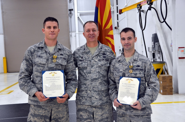 Col. Randall Inman, 161 MXG commander, presents 161st Maintenance Squadron, Staff Sgt. Matthew St. Onge, crew chief and Staff Sgt. Ancel Miller, electrical environmental specialist, with a certificate to accompany their Air Force Commendation Medals Oct., 2016, 161st Air Refueling Wing, Phoenix. The Airmen were awarded the medal for rescuing a woman after a head-on car accident. (U.S. Air National Guard photo/Tech. Sgt. Michael Matkin)