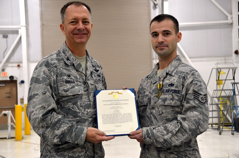 Col. Randall Inman, 161 MXG commander, presents Staff Sgt. Ancel Miller, 161st Maintenance Squadron, electrical environmental specialist, with a certificate to accompany his Air Force Commendation Medals Oct., 2016, 161st Air Refueling Wing, Phoenix. The Airmen were awarded the medal for rescuing a woman after a head-on car accident. (U.S. Air National Guard photo/Tech. Sgt. Michael Matkin)