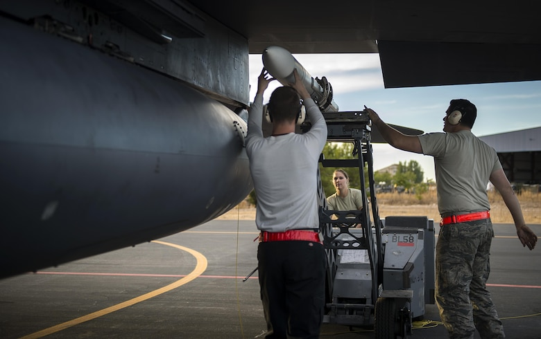 A three-man weapons load crew team, from the 48th Aircraft Maintenance Squadron, load an AIM-120 onto an F-15E Strike Eagle after a sortie in support of Tactical Leadership Programme 16-3 at Los Llanos Air Base, Spain, Sept. 19. The training prepares NATO and allied forces' flight leaders to serve as mission commanders, lead coalition force air strike packages, and provide tactical air expertise to NATO agencies. (U.S. Air Force photo/ Staff Sgt. Emerson Nuñez)