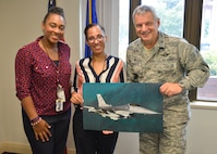 Col. Alan Teauseau, 482nd Mission Support Group commander, presents a Fighter Falcon image to Brittney Odom and Carmen Roman visitors from The Center for Disease Control and Prevention Miami Quarantine station at Homestead Air Reserve Base, Fla., Sept. 26. The station's jurisdiction includes the preclearance ports in Florida, Mississippi, Alabama, the Bahamas and Aruba. (U.S. Air Force photo by Staff Sgt. Desiree W. Moye)