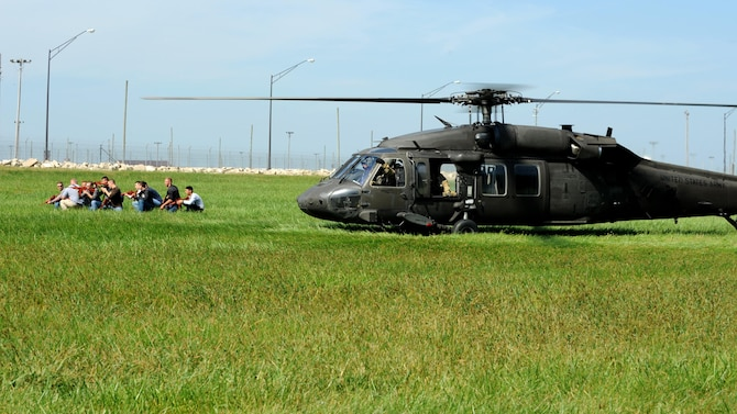 A team of volunteers act as adversaries exiting a UH-60 Blackhawk during training at Whiteman Air Force Base, Mo., Sept. 20, 2016. Their objective was to simulate an attempt to destroy Air Force resources on the flightline. (U.S. Air Force photo by Senior Airman Danielle Quilla)