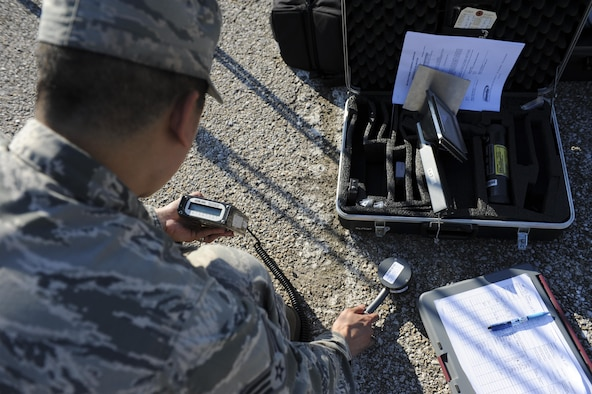U.S. Air Force Senior Airman Emerson Malabuyoc, a bioenvironmental engineering technician with the 509th Medical Operation Squadron, simulates checking for beta radiation on the ground during training at Whiteman Air Force Base, Mo., Sept. 21, 2016. The training tested the emergency responders' ability to handle a possible contamination incident. (U.S. Air Force photo by Senior Airman Danielle Quilla)