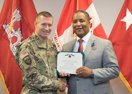 Maj. Gen. Robert Carlson presents Donn Booker with a Department of Army Meritorious Civilian Service Award during a retirement ceremony Sept. 29 in Winchester, Va.