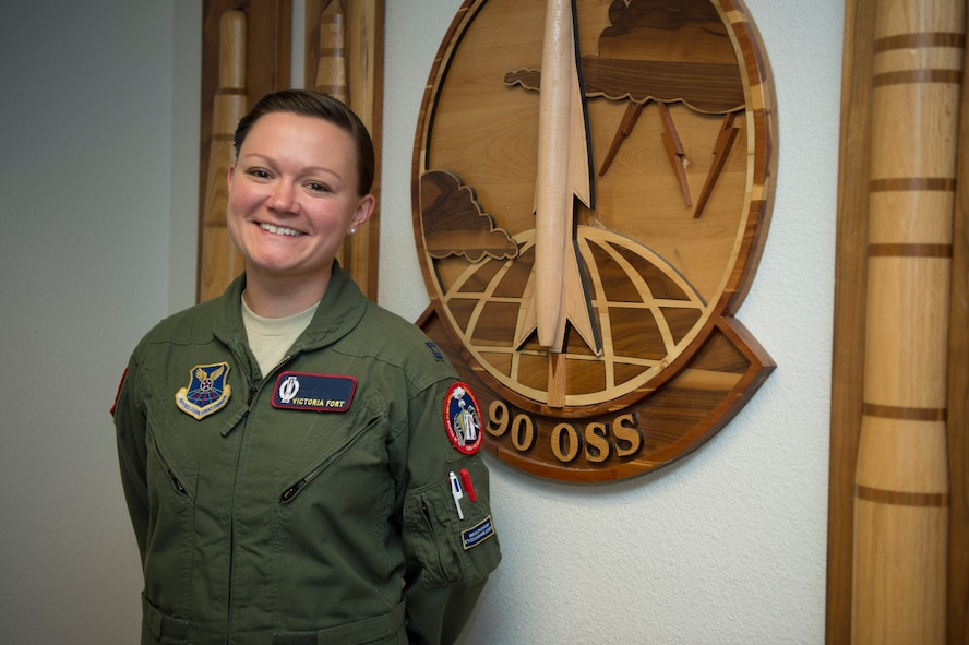 Capt. Victoria Fort, 90th Operational Support Squadron ICBM emergency war order planner, poses for a photo in front of the 90th OSS patch at F.E. Warren Air Force Base, Wyo., Sept. 20, 2016. The 90th OSS is part of the 90th Operations Group, which is charged with the control of 15 Missile Alert Facilities and 150 Minuteman III ICBMs in a 9,600 square mile area covering three states. (U.S. Air Force photo by Staff Sgt. Christopher Ruano)