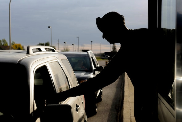 Senior Airman Tyler Serr, an installation entry controller assigned to the 5th Security Forces Squadron, hands back an ID at Minot Air Force Base, N.D., Sept. 30, 2016. Gate sentries vigilantly watch for offenses from minor vehicle infractions to personnel who may have outstanding warrants. (U.S. Air Force photo/Airman 1st Class Jessica Weissman)
