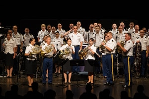 Army Staff Sgt. Selena Maytum (left), U.S. Army Field Band, plays in the horn section playing the National Anthem at a concert.