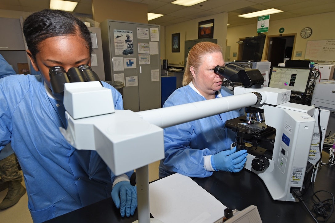 Deanna Adams and Airman 1st Class Cierra Barden, 359th Clinical Laboratory and Radiology Flight medical lab technicians, inspect a blood smear for abnormal cells with a compound microscope at the 359th Medical Group lab at Joint Base San Antonio-Randolph, Texas, Sept. 16, 2016. The compound microscope features an extra viewer to allow for training as well as simultaneous review by technicians. (U.S. Air Force photo/Tech. Sgt. Christopher Carwile/Released)