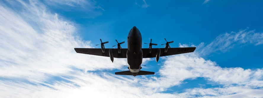 A modified C-130 Hercules soars overhead as it prepares to spray herbicide at the Saylor Creek Training Range, Idaho, Sept. 17, 2016. Two prongs located in its mid-section emit a mixture of water and herbicides to spray large areas. (U.S. Air Force photo by Senior Airman Connor J. Marth/Released)