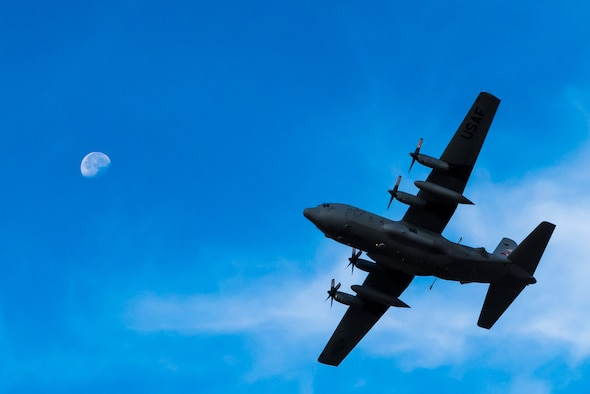 A modified C-130 Hercules banks in front of the moon above the Saylor Creek Training Range, Idaho, Sept. 17, 2016. The aircraft is specifically outfitted to spray hundreds of acres of land with herbicides and water. (U.S. Air Force photo by Senior Airman Connor J. Marth/Released)