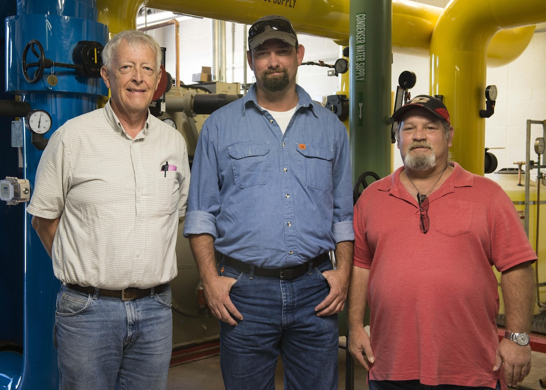Three of the five members of the Dyess Energy Team stand for a group photo at the Dyess Ice Plant during an immersion at Dyess Air Force Base, Texas, Oct. 3, 2016. The Dyess Energy Team recently won a Federal Energy and Water Management Program Award due to taking on three projects that have helped the base cut down on energy usage, money and manpower hours. (U.S. Air Force Photo by Airman 1st Class Katherine Miller/Released)