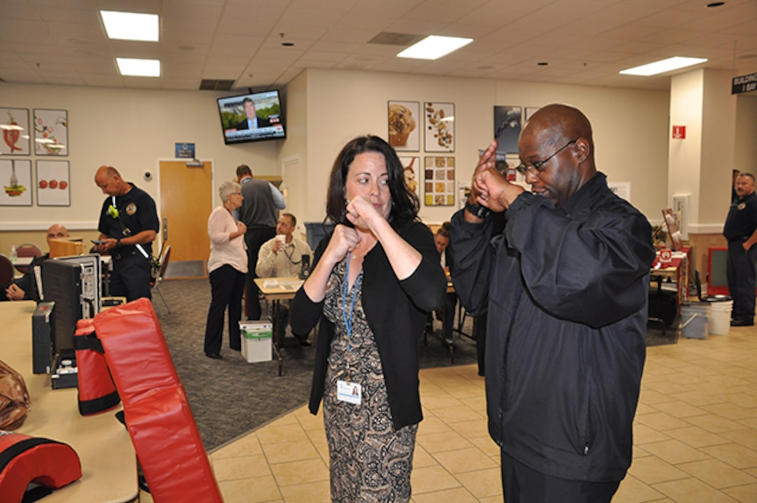 Lt. Bruce Jacobs, Defense Logistics Agency Installation Support at Richmond police training officer, shows Rebecca Bartlett, Virginia Dominion Power, safety chair, the best way to defend against an attacker during a National Preparedness Fair Sept. 28, 2016 at Defense Supply Center Richmond. Bartlett visited the fair to gain insight on conducting one for her organization.