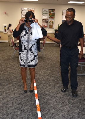 Defense Logistics Agency Installation Support at Richmond, Virginia Police Officer Clarence Jones helps an unidentified employee use the Fatal Vision goggles to experience the effects of driving under the influence during a National Preparedness Fair at Defense Supply Center Sept. 28, 2016. (Photo by Jackie Roberts)