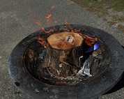 """An A7 business card burns in a fire pit at Hurlburt Field, Fla., Sept. 30, 2016. Air Force Special Operations Command's A4 directorate has absorbed A7. """"It doesn't matter who is in charge, it's about supporting the warfighter … supporting our Air Commandos,"""" said Col. David Piech, AFSOC's last A7 director, at the Irish Wake-themed ceremony. (U.S. Air Force photo/Staff Sgt. Melanie Holochwost)"""