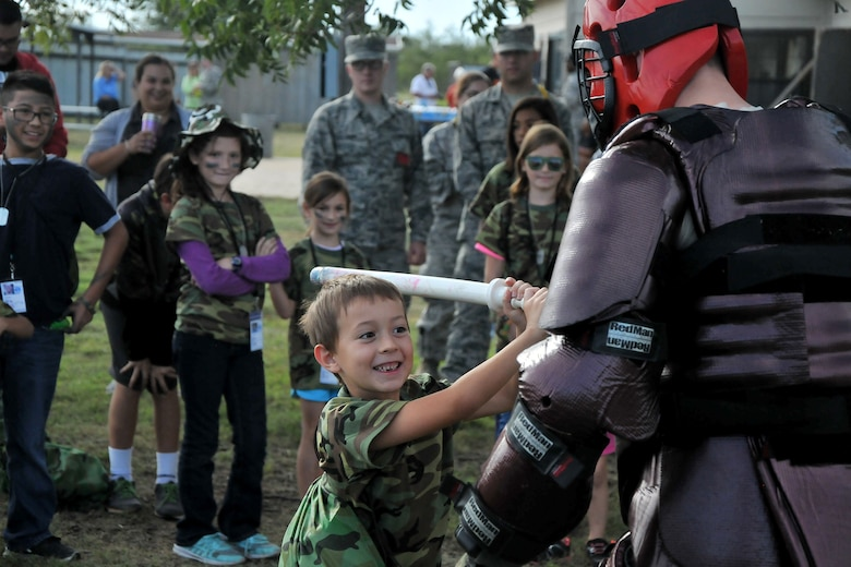 A child swings a dummy baton at a padded Airman during Operation Kids Investigating Deployment Services at the 17th Force Support Squadron on Goodfellow Air Force Base, Texas, Oct. 1, 2016. The 17th Security Forces Squadron gave the children mock pre-deployment training. (U.S. Air Force photo by Airman 1st Class Randall Moose/Released)