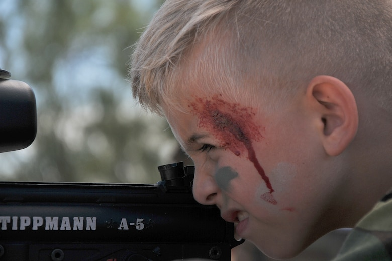 A child, wearing face-paint, fires a paint-ball gun during Operation Kids Investigating Deployment Services at Camp Sentinel on Goodfellow Air Force Base, Texas, Oct. 1, 2016. Operation KIDS volunteers taught the children how to aim and fire paint-ball guns. (U.S. Air Force photo by Airman 1st Class Randall Moose/Released)