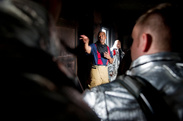 U.S. Air Force Master Sgt. Darnell Walls, 51st Civil Engineer Squadron assistant chief of training, instructs firefighters during a training scenario at Camp Humphreys, Republic of Korea, Sept. 28, 2016. The scenario was a biannual structural firefighting training designed to train in building fires. (U.S. Air Force photo by Staff Sgt. Jonathan Steffen)