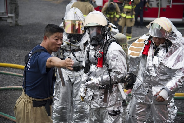 U.S. Air Force Master Sgt. Hungpyo Rucci, 51st Civil Engineer Squadron assistant chief health and safety, gives instructions to firefighters during a training scenario at Camp Humphreys, Republic of Korea, Sept. 28, 2016. Mongrel firefighters used Humphreys' fire training facilities to maintain currency on their training for structural fires. (U.S. Air Force photo by Staff Sgt. Jonathan Steffen)