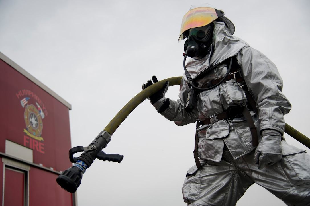 A U.S. Air Force firefighter from the 51st Civil Engineer Squadron holds a hose and nozzle during structural firefighting training at Camp Humphreys, Republic of Korea, Sept. 28, 2016. The 51st CES fire prevention team practiced tactics and techniques for structural fires during the training scenario. (U.S. Air Force photo by Staff Sgt. Jonathan Steffen)
