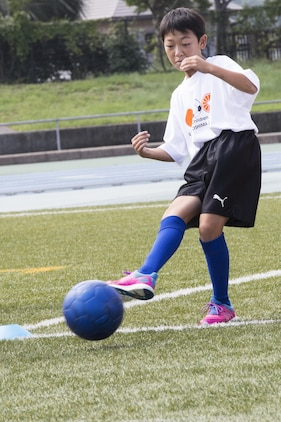 A local Japanese child kicks a ball during a soccer drill at the U.S.-Japan Children Soccer event at the Suo-Oshima Athletic Field in Suo-Oshima, Japan, Oct. 1, 2016. The soccer drill tested the children's accuracy and ability to score at different lengths of the field. While cheering each other on, players aimed to kick the ball at 30 meters into a goal through cones simulating defenders. (U.S. Marine Corps photo by Lance Cpl. Joseph Abrego)