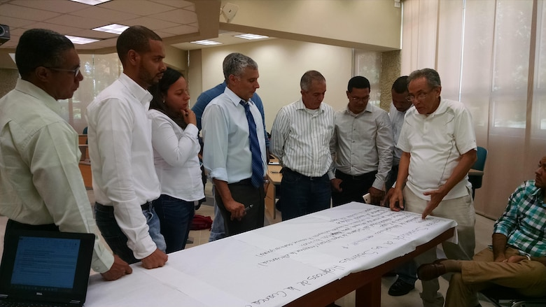 Dominican PMP team members with IWR's Dr. Guillermo Mendoza (center) viewing the prioritized list of the most important problems facing the upper, middle, and lower sub-basins within the Yaque del Norte basin.