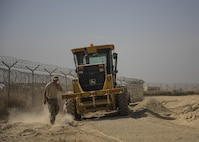 """Senior Airman Austin DeDeo, 455th Expeditionary Civil Engineer Squadron pavements and heavy equipment technician, checks his work after leveling gravel, Bagram Airfield, Afghanistan, Oct. 4, 2016. The ECES """"Dirt Boys"""", as they are known, laid down gravel to start the foundation for a new road. The road, which will provide a pathway for mine-resistant ambush-protected (MRAP) vehicles, will be built around the fence line of the airfield and utilized by security forces as a means to secure the flightline. (U.S. Air Force photo by Senior Airman Justyn M. Freeman)"""
