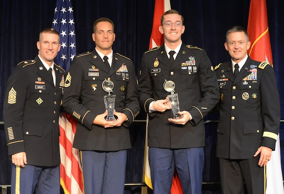 NCO of the Year Sgt. 1st Class Joshua Moeller (second from left) and Soldier of the Year Spc. Robert Miller hold their Best Warrior trophies presented by Sgt. Maj. of the Army Daniel Dailey (left) and Vice Chief of Staff of the Army Gen. Daniel Allyn at the AUSA awards luncheon in the Washington Convention Center, Oct. 3, 2016.