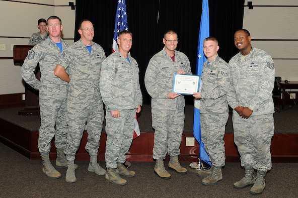 Senior Airman Bryan Krick, 22nd Communications Squadron network infrastructure technician, poses with Col. Phil Heseltine, 22nd Air Refueling Wing vice commander, and 22nd CS leadership, Sept. 30, 2016, at McConnell Air Force Base, Kan. Krick received the spotlight performer for the week of Sept. 19-23. (U.S. Air Force photo/Senior Airman David Bernal Del Agua)