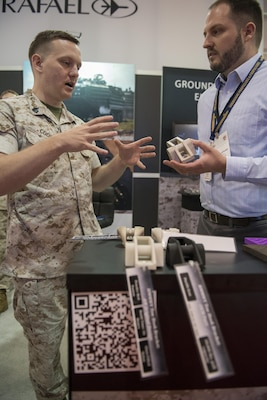 160928-N-IL267-003 QUANTICO, Virginia (Sept. 28, 2016) Marine Sgt. Stephen Cook, a legal service specialist with Headquarters Marine Corps, Judge Advocate Division, and amateur hobbyist 3-D printer, and Jonathan Hopkins, a member of the Additive Manufacturing Tiger Team and employee of Naval Surface Warfare Center, Carderock Division, discuss 3-D printed parts at the Modern Day Marine Expo at Marine Corps Base Quantico, Va. Naval Sea Systems Command, Naval Aviation Systems Command, Marine Corps Systems Command, the Marine Corps Warfighting Laboratory, and Marine Corps Headquarters, Installations and Logistics Department collaborated on an additive manufacturing parts demonstration at the expo. (U.S. Navy photo by Dustin Q. Diaz/released)