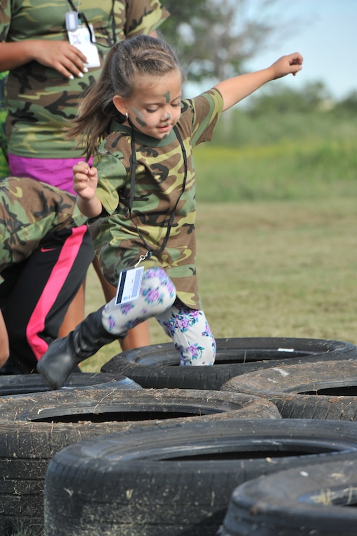 A child runs through tires as part of 17th Security Forces Squadron training during Operation Kids Investigating Deployment Services at the 17th Force Support Squadron Lodge, Goodfellow Air Force Base, Texas, Oct. 1, 2016. The 17th Security Forces Squadron used multiple stations to train the youths for their deployment. (U.S. Air Force photo by Staff Sgt. Laura R. McFarlane/Released)