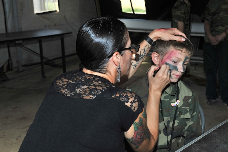 Cecilia Diaz, 17th Medical Group Family Advocacy outreach manager, paints a child's face to look like an injury during Operation Kids Investigating Deployment Services at Camp Sentinel, Goodfellow Air Force Base, Texas, Oct. 1, 2016.  Other events at Camp Sentinel included a Marine obstacle course, and paintball shooting and grenade throwing with the Army. (U.S. Air Force photo by Staff Sgt. Laura R. McFarlane/Released)