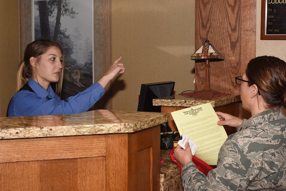 Katelyn Brooks, Malmstrom Inn desk services representative, assists a guest to check in at the inn at Malmstrom Air Force Base, Mont., Sept. 23, 2016.  The 83-room lodging facility has units available for active duty and retired Department of Defense members and their families.  (U.S. Air Force photo/Jason Heavner)
