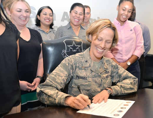 Brig. Gen. Heather L. Pringle, 502nd Air Base Wing and Joint Base San Antonio commander, signs a proclamation designating October as Domestic Violence Awareness Month Sept. 13 in the JBSA-Fort Sam Houston conference room, surrounded by members of the JBSA Family Advocacy staff.