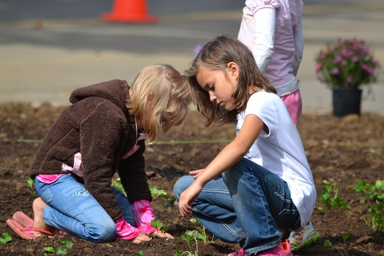 Two young girls work in a garden bed at the Cheatham Lake Resource Manager's Office during a National Public Lands Day event Oct. 1, 2016. Cheatham County Master Gardeners orchestrated planting bee-and-butterfly-friendly plants.