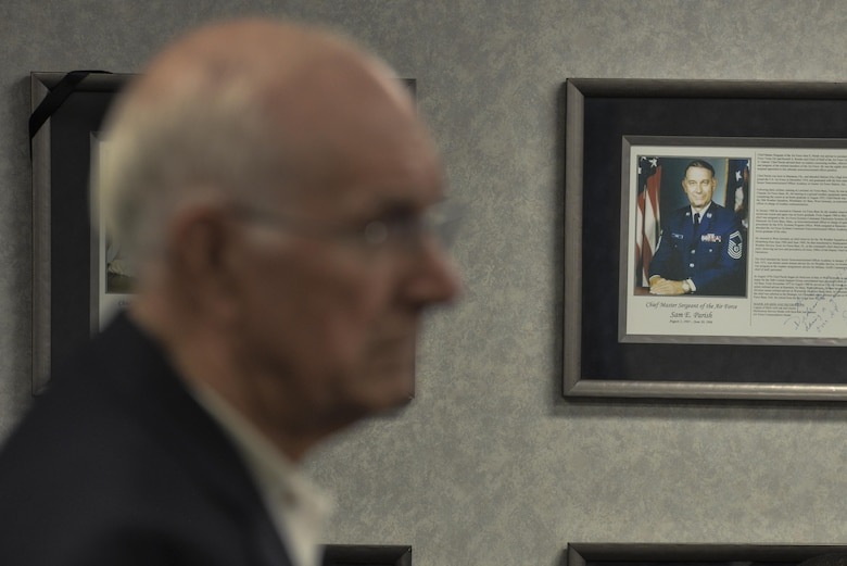 An image of the eighth chief master sergeant of the Air Force, Sam Parish hangs on the wall as he speaks to the students in Airman Leadership School class 2016-G Oct. 3, 2016 at Fort George G. Meade, Md. Serving for nearly 20 years at the rank of CMSgt, Parish gave his outlook on the history of enlisted history and how Airmen are able to make a change to improve the Air Force during his visit. (U.S. Air Force photo/Staff Sgt. Alexandre Montes)